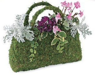 A purse made of greenery with flowers bursting out